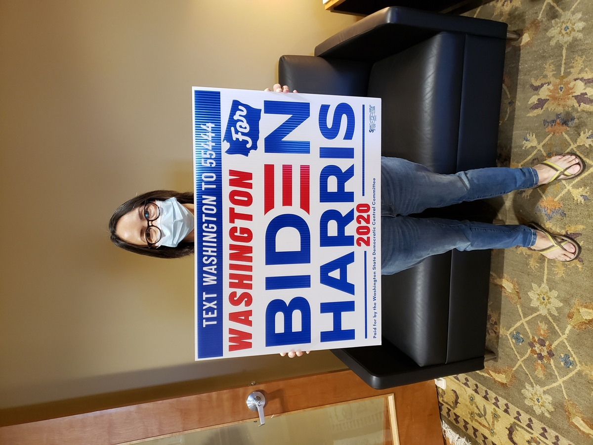 Picture of happy voter with a Biden/Harris Yard Sign in hand.